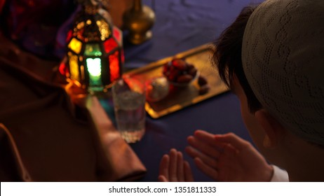 Man praying. Breaking the fast. Fasting the month of Ramadan. Iftar: the Daily Break Fast During Ramadan