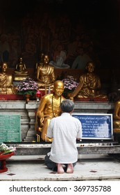 Man praying at a Buddhist temple in Thailand.