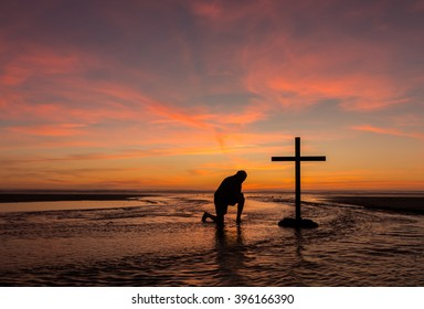 A man praying by a black cross with a flowing stream water around it, at a beach with the sunset sky.