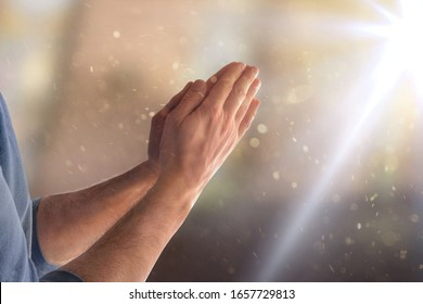 Man praying in church with hands with palms facing and flash of light. Horizontal composition
