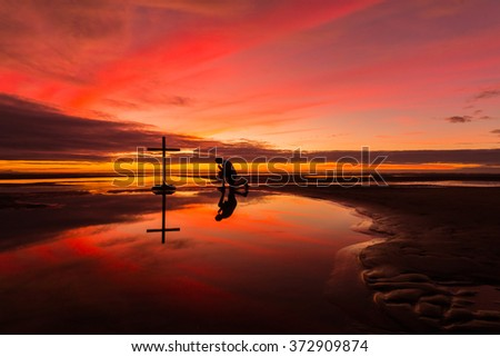 Man praying at a cross on a beach with a wonderful sunset sky behind him.