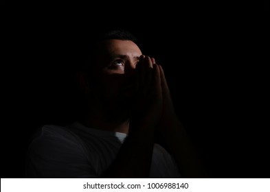 man praying to God in the dark room over concrete wall with window light effected, can be used for christian background or trust concept, copy space. Prayer on a black background in a white t-shirt