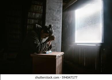 Man Praying to God in Dark Room  with Window Light