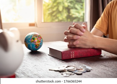Man praying to God with globe model, Holy Bible, and a group of coins in the room