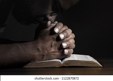 Man praying to God on a Bible in a dark place.
