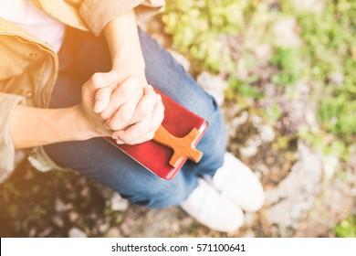 man praying on holy bible in the morning.teenager man hand with Bible praying,Hands folded in prayer on a Holy Bible in the garden concept for faith, spirituality and religion
