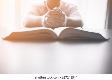 man praying on holy bible in the morning.teenager boy hand with Bible praying,Hands folded in prayer on a Holy Bible in church concept for faith, spirituality and religion
