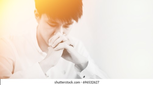 man praying on holy bible in the morning.teenager boy hand with Bible praying,Hands folded in prayer on a Holy Bible in church concept for faith, spirituality and religion.