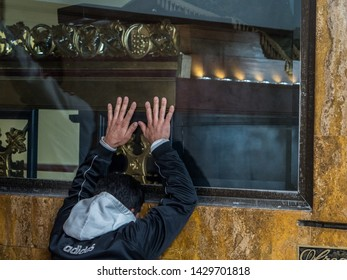 """Man is praying in sanctuary """"El Senor Caido"""" from the 17th century on the Monserrate hill in Bogota,  Sanctuary of Christ falling under the cross, Colombia, South America"""