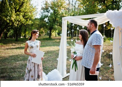Man with pregnant woman and master of ceremony stay background white arch on garden