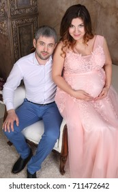 Man and pregnant woman in pink dress sits on baroque armchair in studio, top view