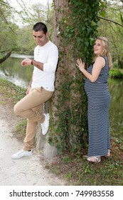 a man and a pregnant woman play in the park
