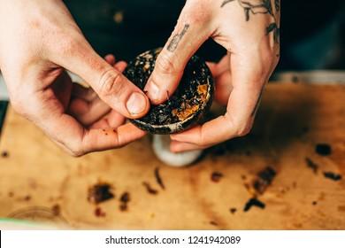 A man prepare hookah sisha in hookah art bar. Tabaco preparation.