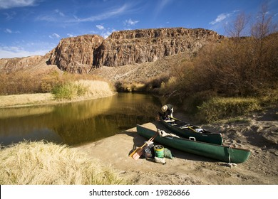 A man prepares a canoe to go down the Rio Grande near Terlingua, Texas.  The person is standing in the United States, while Mexico is the other side of the river.