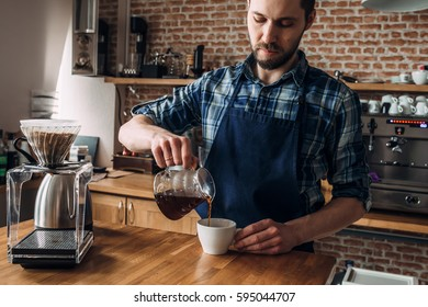 "Man prepares coffee in the style of ""pour over"" in the barista school. Against the background of coffee equipment and a brick wall"