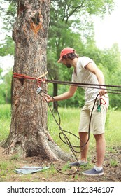 Man prepares the equipment fixes secures the rope to the tree for slacklining