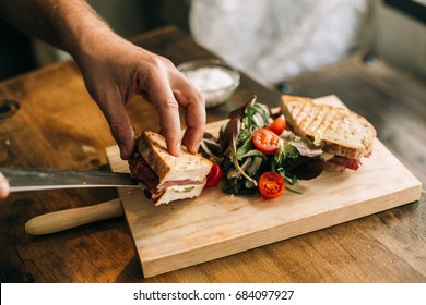 Man prepares lunch, serves grilled bread sandwich snack on top of wooden cutting board, with side of green salad, healthy alternative to burgers and grease