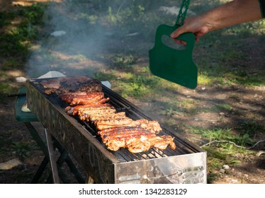 Man preparing bbq (sausages, pork steaks, kebabs, beef burgers, chicken breasts etc) on the grill. Picnic concept. Backyard party background.