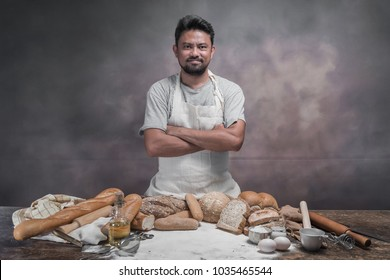 Man preparing buns at table in bakery, Man sprinkling flour over fresh dough on kitchen table