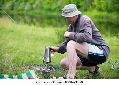 man preparing coffee at a picnic, Ukraine, city of Chernigov, June 2017  editorial