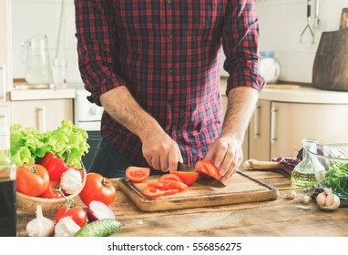 Man preparing delicious and healthy food in the home kitchen on a sunny day
