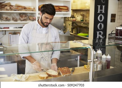 Man preparing food behind the counter at a sandwich bar