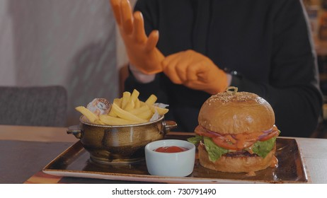 Man preparing for food at fast food restaurant. Burger with french fries and sauce at the table and guy wearing gloves before start eat.