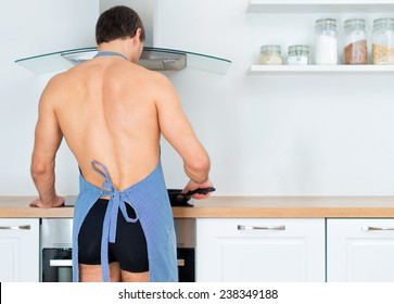 Man preparing food in the kitchen. View from the back.