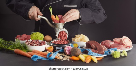 Man preparing fresh health barf food for his dog with a selection of fresh vegetables, heart, stomach, offal, organs, poultry and beef processing them through an old meat grinder