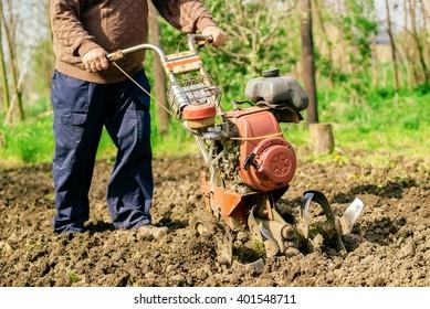 Man preparing garden soil with cultivator tiller, new seeding season on home vegetable farm