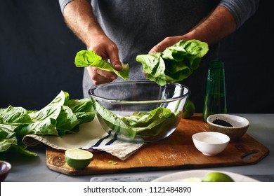 Man is preparing green salad of romaine lettuce. Healthy food concept