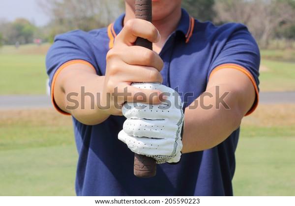 Man preparing to grip a golf club