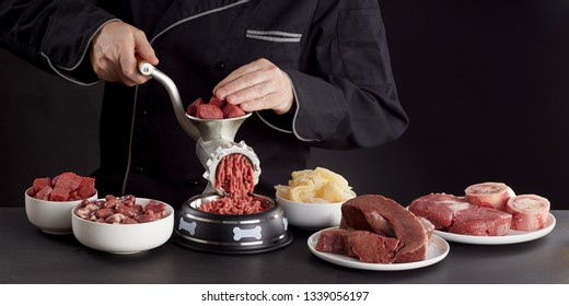 Man preparing healthy raw meat for barf dog food passing a selection of fresh heart, stomach, lungs, offal, poultry, visceral and organs through an old vintage manual meat grinder