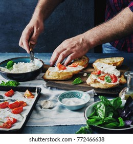 Man preparing Italian bruschetta with baked tomatoes, basil and cheese. Italian food