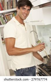 Man Preparing Meal At Cooker