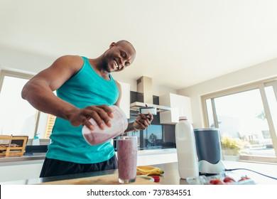 Man preparing milk shake in kitchen. Smiling man pouring milkshake in a glass for drinking.