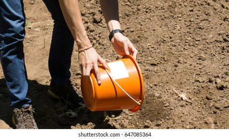 A man is preparing for planting on the very dry ground, lower half body.
