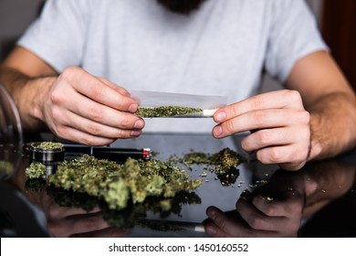 Man preparing and rolling marijuana cannabis joint. Close up of addict lighting up marijuana joint with lighter. Man rolling a marijuana joint. Drug use. Close up. Drugs narcotic concept.