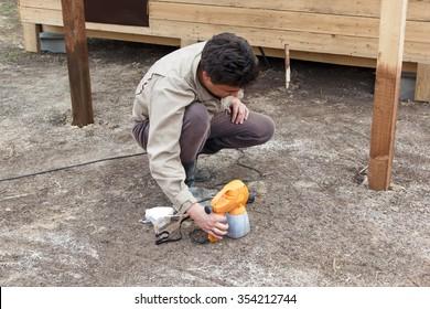 man preparing spray gun for painting wooden structure