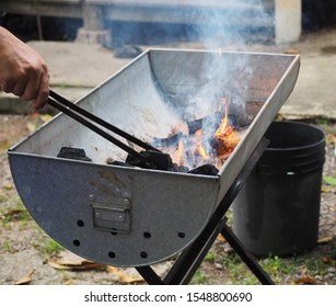 The man is preparing the stove for cooking