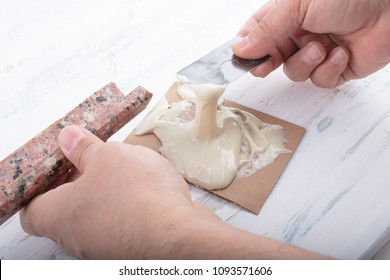 Man preparing two component adhesive for repairing marble  in a close up view of his hands in a concept of DIY repairs with copy space