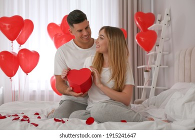 Man presenting gift to his girlfriend in room decorated with heart shaped balloons. Valentine's day celebration