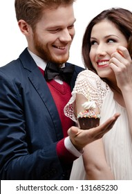 Man presents birthday cake to his pretty girlfriend who likes it very much, isolated on white
