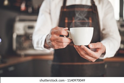 Man presents cup of hot coffee at cafe, coffee shop business