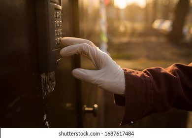 A man presses a doorphone button in a medical glove. Precautions against virus infection. Hand in medical glove and intercom closeup photo.