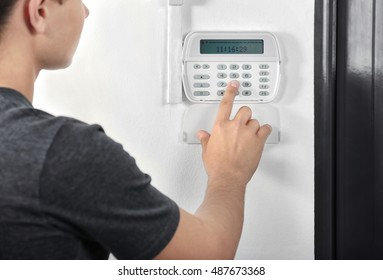 Man pressing the code on a house alarm