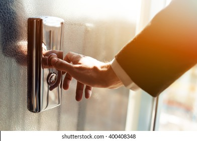 Man pressing elevator button. finger presses the elevator button. Red button. sunset light. businessman is a lift. high floor. hand reaches for the button of the elevator call.