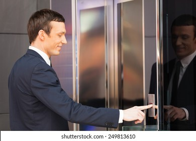 Man pressing red elevator button. side view of businessman pushing elevator button