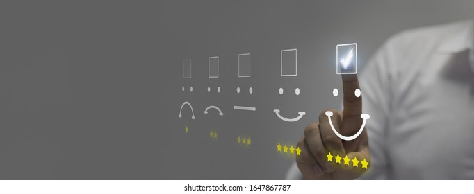 man pressing smiley face emoticon on virtual touch screen.