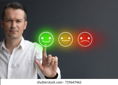 Man pressing smiley face emoticon on digital touch screen. Customer service evaluation concept.